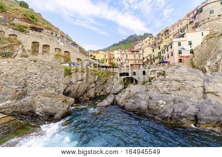 Manarola town Riomaggiore La Spezia province Liguria northern Italy. View of the colourful houses on surrounding hills sea shore balconies and windows. Part of the Cinque Terre National Park and a UNESCO World Heritage Site.