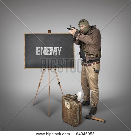 Enemy text on blackboard with terrorist holding machine gun