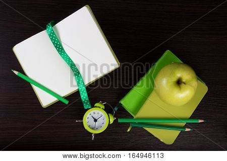 Notebooks pencils clock and apple on dark wooden background. Different tints of green. Top view. Flat lay. Can be used as a field for notes notebook cover.