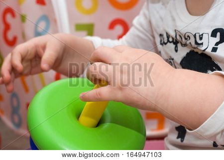 Baby with multicolour piramid toy on the numbers background