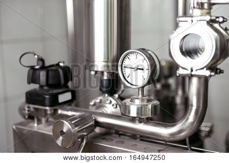 Best equipment. Brewing mechanisms consisting of pipes and gauges standing on a beer factory and being used.