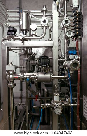 Use it properly. Close up of brewing mechanisms consisting of pipes and gauges standing on a beer factory and being used.