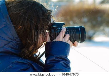 Young woman taking a photo outdoor on winter