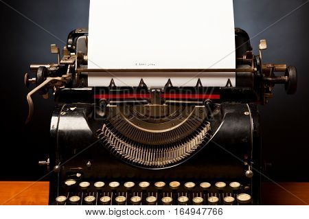 typewriter with the sentence 'I love you' on an otherwise empty sheet of paper