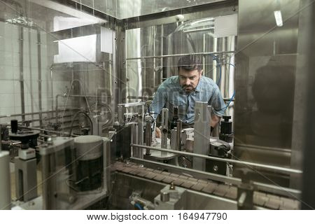 Attentive worker. Concentrated young handsome man controlling products while working on brewing factory and using special mechanisms.
