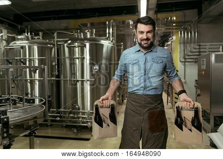 Delighted brewer. Happy young handsome man holding bottles of alcohol while standing in brewery and smiling.