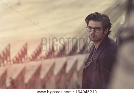 Intellectual man with eyeglasses outdoor. Retro colors. Charming and handsome young man with glasses looking. Black hair. Winter jacket. Urban outdoors scene with antique colors.