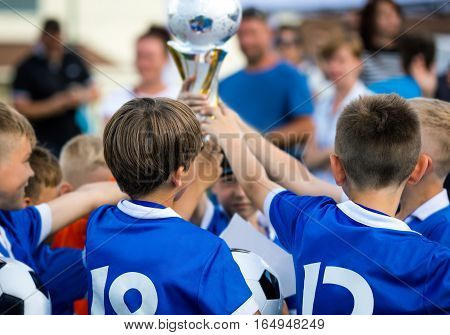 Young Soccer Players Holding Trophy. Children Soccer Football Champions. Boys Celebrating Soccer Championship. Winning Team of Sport Kids Tournament. Youth Soccer Cup Winners Parents in the Background