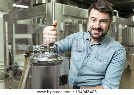 Taste it. Delighted handsome young man pouring alcohol while spending time in brewery and working.