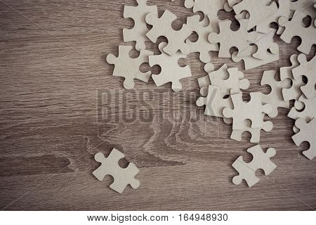 Top view of mixed pieces of a jig saw puzzle placed on the wooden surface