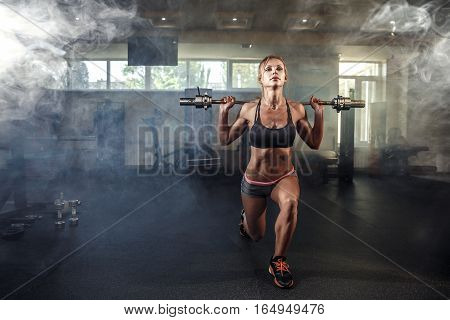 Young sexy girl in the gym doing squats on smoke background