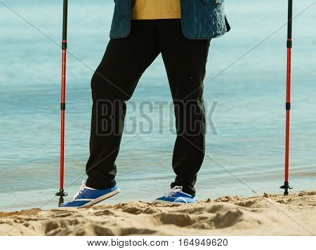 Healthy lifestyle in old age. Senior woman practicing nordic walking on sandy beach. Active elderly female enjoying sunny day.