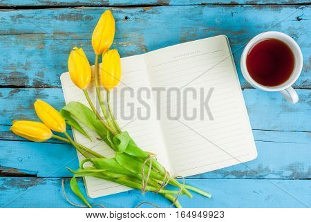 Tea, Tulips And Notebook On Blue Table