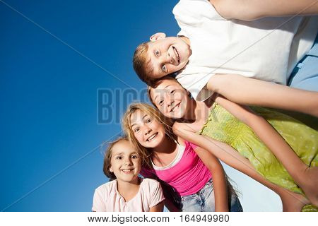 four happy beautiful children looking at camera from top in the sunny summer day and blue sky. looking at camera with funny face and toothy smile. view from below.