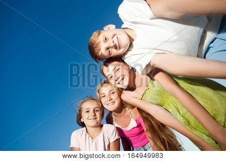 four happy beautiful children looking at camera from top in the sunny summer day and blue sky. looking at camera with funny face and toothy smiles. view from below.