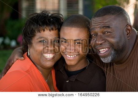 Portrait of an African American grandparents hugging their grandson.