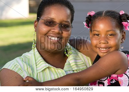 African American mother and daughter smiling and hugging.