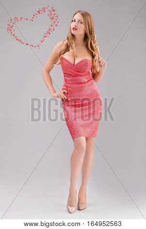blond woman in red polka dot dress on gray background
