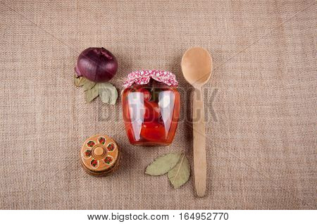 Top view. Still life. Tomatoes in transparent glass jar covered by cloth wooden round box with pattern red onion bay leaves and big wooden spoon lay on sackcloth as background