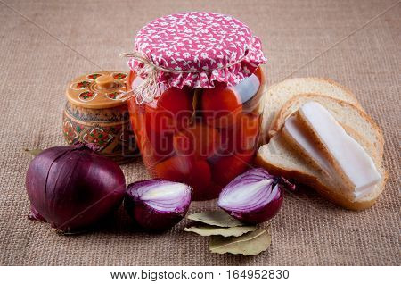 Authentic ukrainian Still Life. Transparent glass jar with tomatoes inside covered by red cloth red onion wooden round box with pattern slices of bread and lard bay leaves lay on sackcloth as background