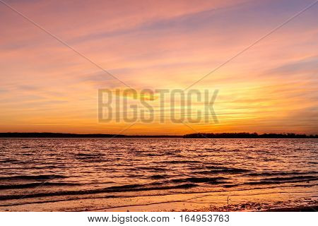 An almost pink and yellow sunset over a lake in Oklahoma.