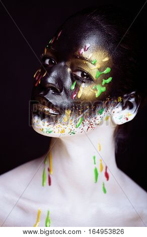 woman with creative makeup closeup like drops of colors, facepaint splashes close up halloween