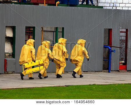 A group of four rescuers in the protective clothing in the industrial accident