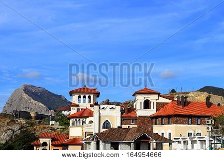 Homes on the hillside on the background of rock