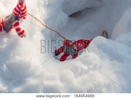 Small wooden toys in the rescue scene and assist doll pulls a rope from a snowy ravine another doll