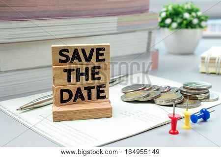 Text message Save the date on wooden with book bank, stacked coins. Finance concept