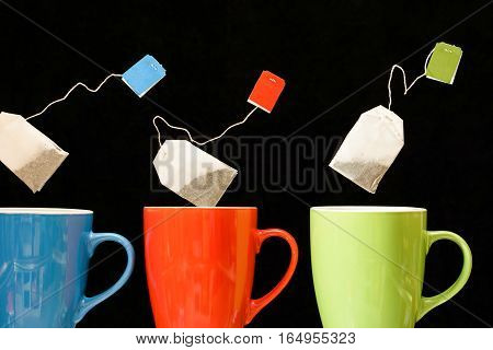 Row of tea cups with teabags falling motion inside on dark background - Colorful line of mugs with dropping flavoured herb infusion - Close up image with black copy space