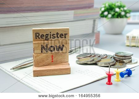 Text message Register now on wooden with book back, Finance concept