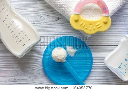 preparation of mixture baby feeding on wooden background top view.