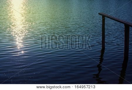 Wooden pier at sunset with beutiful sparking lights on the lake sea ocean surface and beautiful blue water color