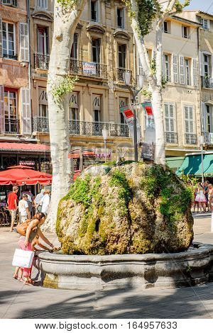 AIX-EN-PROVENCE FRANCE - JUL 17 2014: Mother and daughter having fun at the fountain stone in center of Aix-En-Provence on a warm summer day enjoying the atmosphere on Boulevard Napoleon