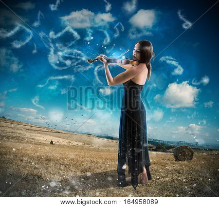 Elegant woman playing the violin on background of countryside with musical notes