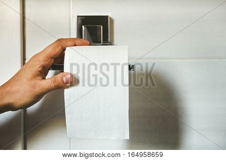 Hand picks a white toilet paper that hangs on the wall in the bathroom