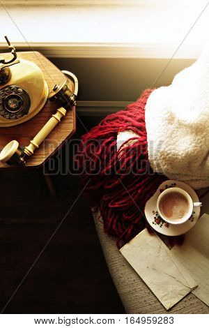 Vintage telephone on wooden table. Chair with cozy blanket with teacup and letter.