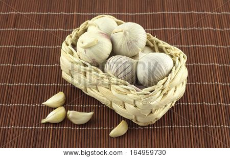 Ripe fragrant garlic in wicker basket on straw mat close up
