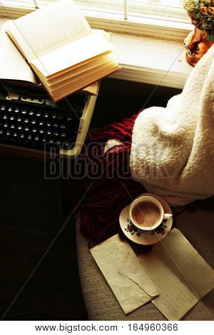 Cozy chair and blanket, vintage teacup, letter, open book, and typewriter by windowsill