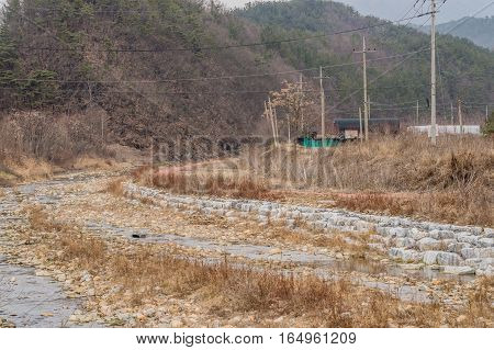 Dried riverbed with rocky shoreline and tree covered hills in the background
