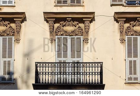 Balcony, stucco, shutter and wrought iron balusters in Nice on the French Riviera