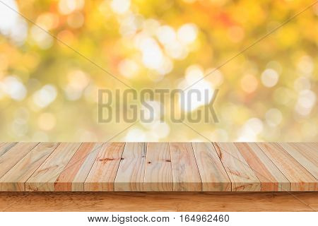 Empty wood table with bokeh abstract yellow background. For display or montage your products.