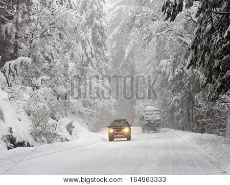 Road with cars in winter forest. Heavy snow.