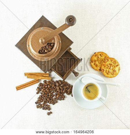 Coffee cup, biscuit grinder and coffeebeans on table.