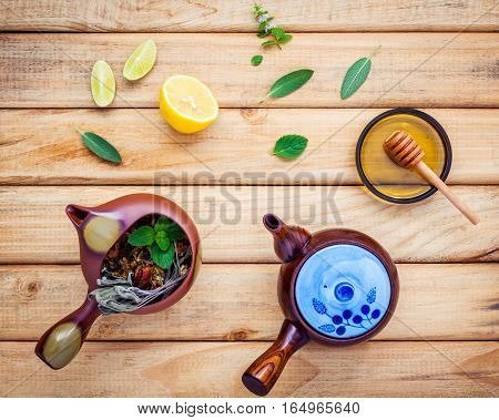 Assortment of dried herbal tea. Herbal tea pots with fresh herbs sage peppermint honey lime and lemon on rustic wooden background with flat lay.