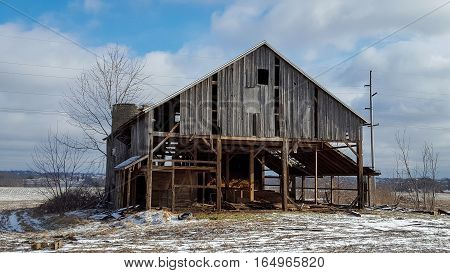 old abandoned weathered wooden barn in winter