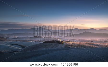 Volterra winter panorama rolling hills and green fields on blue sunset. Tuscany Italy Europe