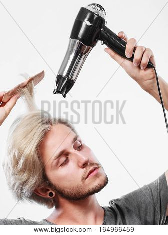 Young Man Drying Hair With Hairdryer