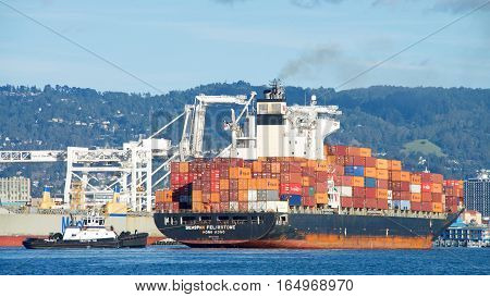 Oakland CA - January 01 2017: Tugboat AHBRA FRANCO pulling on the stern of cargo ship SEASPAN FELIXSTOWE assisting the vessel to turn prior to docking at the Port of Oakland.